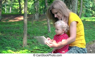 woman with cute baby girl using tablet computer in park.