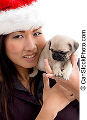 woman with cute puppy and christmas hat