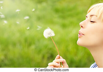 A picture of a woman blowing a dandelion over green background