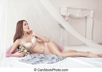 Woman with dark hair in lingerie lying on the bed