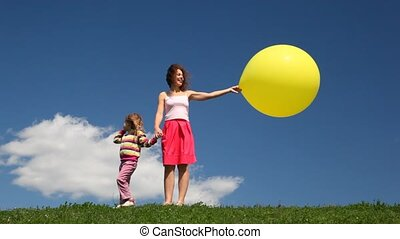 Woman with daughter and bubble stand on grass
