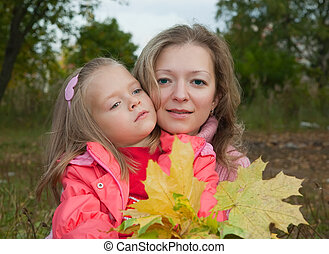 Woman with daughter in autumn