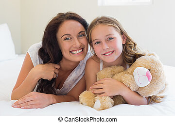 Woman with daughter lying in bed