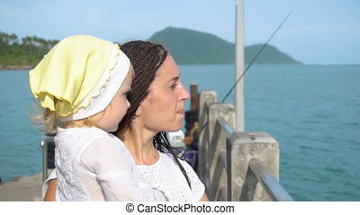 Woman with daughter on pier
