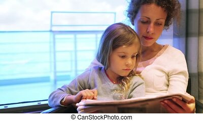 Woman with daughter sit in chair and reads newspaper at cabin