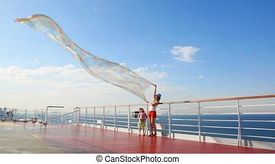 woman with daughter stands on deck and holds fabric