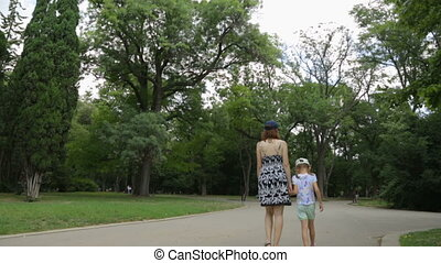 Woman with daughter walking in park