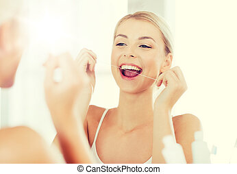 woman with dental floss cleaning teeth at bathroom