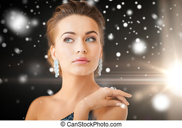 jewelry, luxury, vip, nightlife, party concept - beautiful woman in evening dress wearing diamond earrings