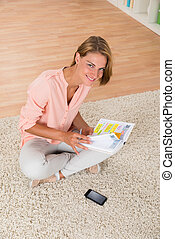 Woman With Diary Sitting On Carpet