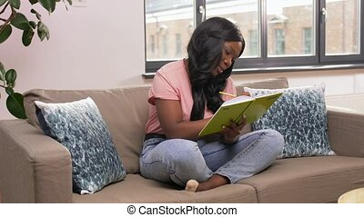 woman with diary sitting on sofa at home - people and ...