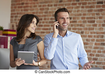 Woman with digital tablet and man with a phone