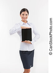 Woman with digital tablet. Cheerful young woman in formalwear holding a digital tablet while isolated on white