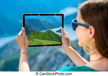 Woman with digital tablet on the top of mountain