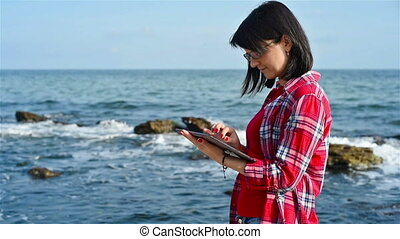 Woman with digital tablet on a ocean background