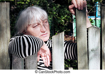 Woman with short gray hair waiting with a distant gaze behind the rustic fence. Outdoor portrait