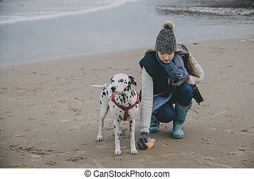 Woman With Dog On A Winter Beach