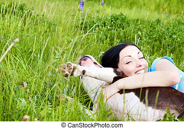 woman with dog playing in the grass
