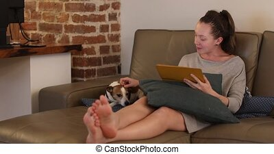 Woman with dog using tablet on sofa - Happy beautiful woman...