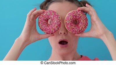 Woman with donuts surprised - Woman is holding donuts in her...