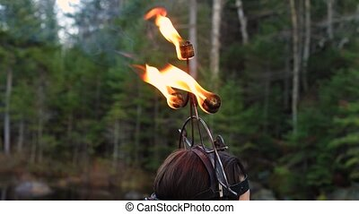 Selective focus of young woman dancer wearing dragon helmet with illuminated and sparkling fire on fire staff dancing during fire jamming in Canada