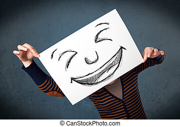 Woman with drawed smiley face on a paper in front of her...