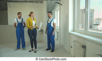 Woman with drawing in hands shows a flat to repairmen