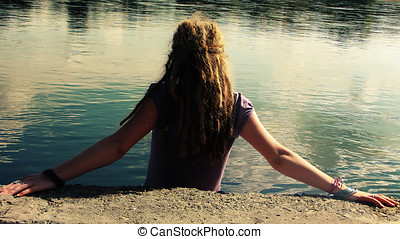 woman with dreadlocks near the water, back...