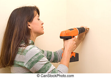 Woman with drill - A young Woman using a cordless drill.