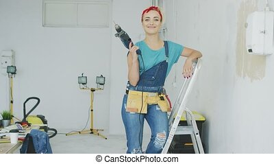Woman with drill standing on stepladder