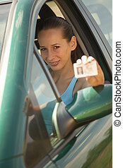 woman holding driving licence in a car into the camera