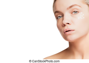 Woman with drops of cream on her face