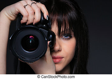 Woman with DSLR - Young woman with DSLR over dark background...