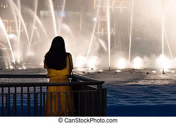 Woman with Dubai mall fountain show view
