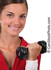 Woman with dumbbell in hand
