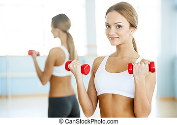 Woman with dumbbells. Beautiful young woman holding dumbbells and smiling at camera