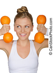 woman with dumbbells from oranges looking away