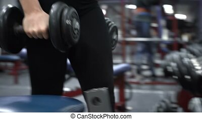 Woman with dumbbells in fitness gym