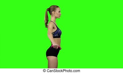 Woman with dumbbells in profile. Slow motion. Green screen