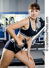 Woman with dumbbells in sports club