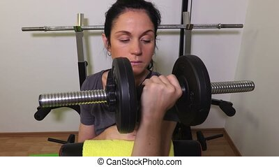 Woman with dumbbells on bench