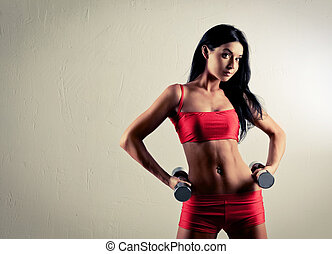 woman with dumbbells - studio portrait of a beautiful sporty...