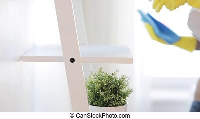 woman with duster cleaning shelf from dust at home