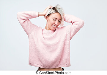 Woman with dyed hair, dressed in pink sweater, looking with satisfaction at camera, being happy.