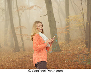 Woman with earphones listening to music in park.