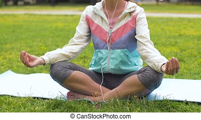 woman with earphones meditating at park - fitness, sport and...