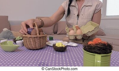 Woman with Easter eggs near table