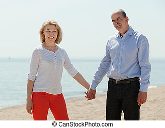 woman with elderly man together against sea