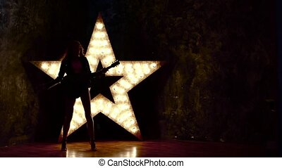 woman with electric guitar. sexy girl in leather, shining star in the background. slow motion, silhouette