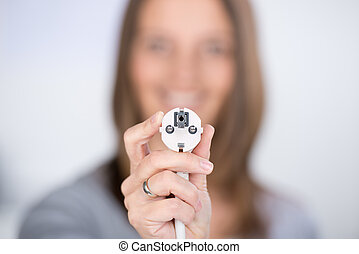 Closeup of smiling mid adult woman with electric plug at home